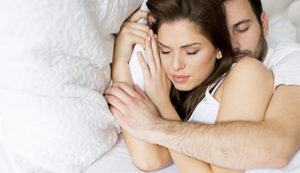 Man hugging his wife in a comfortable mattress while sleeping