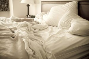 White lush sheets on an unmade bed